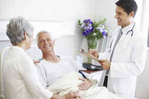 An elderly couple receiving positive news from a doctor